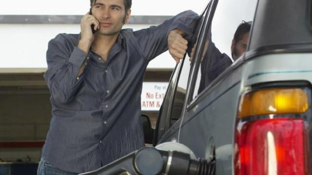 Man using phone while refuelling.