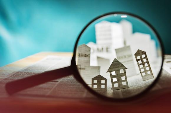 Magnifying glass showing paper cutouts of homes.
