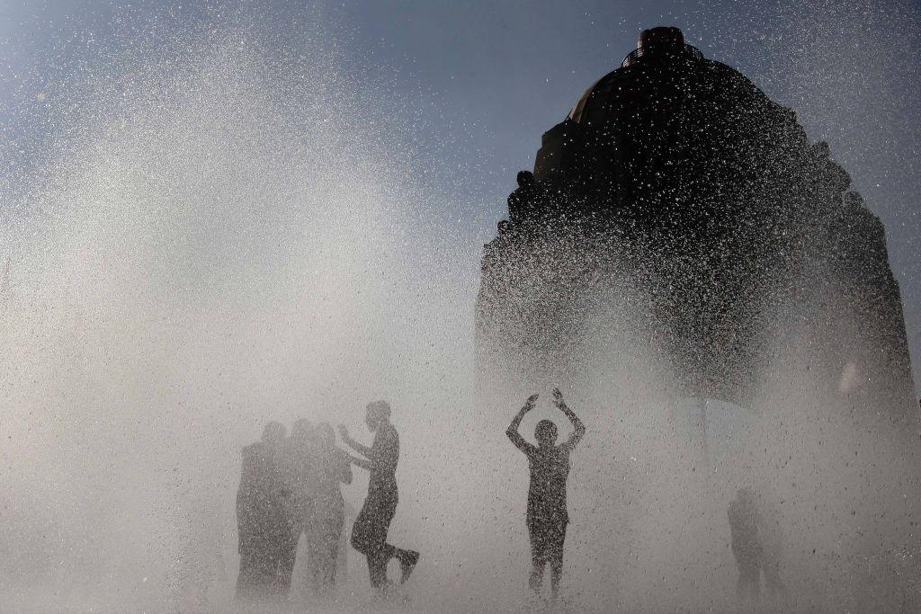 MEXICO: Youths play in a fountain at Mexico City's Monument to the Revolution.