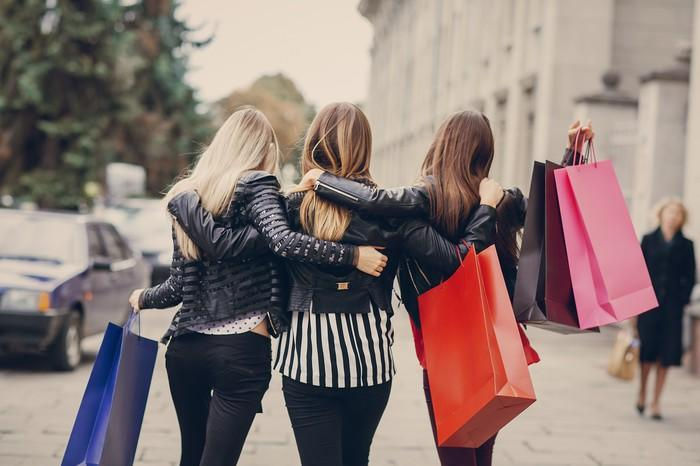 The backs of three women with their arms around each other and holding shopping bags while walking down a street.