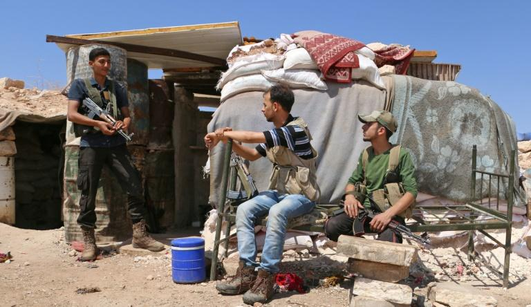 Syrian rebel fighters of the Turkish-backed National Liberation Front rest in the northern countryside of Idlib province on September 5, 2018, as a threatened government offensive looms