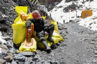 An artisanal gold miner sits on sacks of stones from a gold mine, before it is processed to extract gold, in La Rinconada, in the Andes