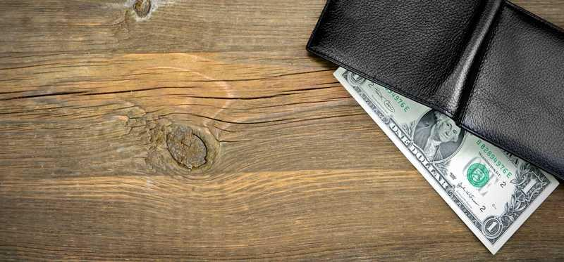 A one dollar bill in a wallet on a table.