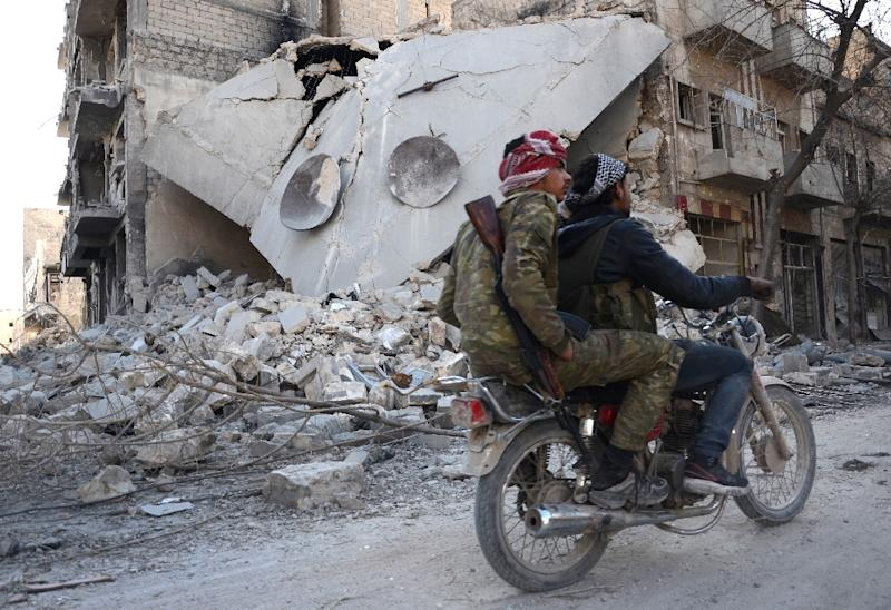 Rebels ride a motorcycle past a destroyed building in the northwestern Syrian border town of al-Bab on February 25, 2017 (AFP Photo/Nazeer al-Khatib)