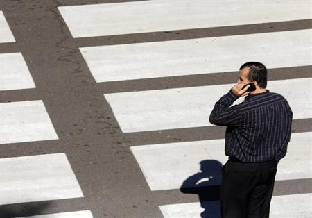 A man talks on his mobile phone as he waits at a crosswalk at Lindbergh Field Airport in San Diego