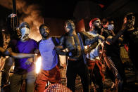 In this image released by World Press Photo, Thursday April 15, 2021, by John Minchillo, Associated Press, part of a series titled Minneapolis Unrest: The George Floyd Aftermath, which won third prize in the Spot News Stories category, shows Protesters join arms in defiance during a demonstration outside the burning Minneapolis Police Department 3rd Precinct building, in Minneapolis, Minnesota, USA, on 28 May 2020. (John Minchillo, Associated Press, World Press Photo via AP)