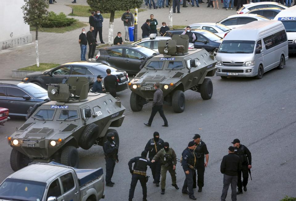 "Georgian police gather at a bank where an armed assailant took several people hostage in the town of Zugdidi in western Georgia, Wednesday, Oct. 21, 2020. An armed assailant took several people hostage at a bank in the ex-Soviet nation of Georgia on Wednesday, authorities said. The Georgian Interior Ministry didn't immediately say how many people have been taken hostage in the town of Zugdidi in western Georgia, or what demands the assailant has made. Police sealed off the area and launched an operation ""to neutralize the assailant,"" the ministry said in a statement. (AP Photo/Zurab Tsertsvadze)"