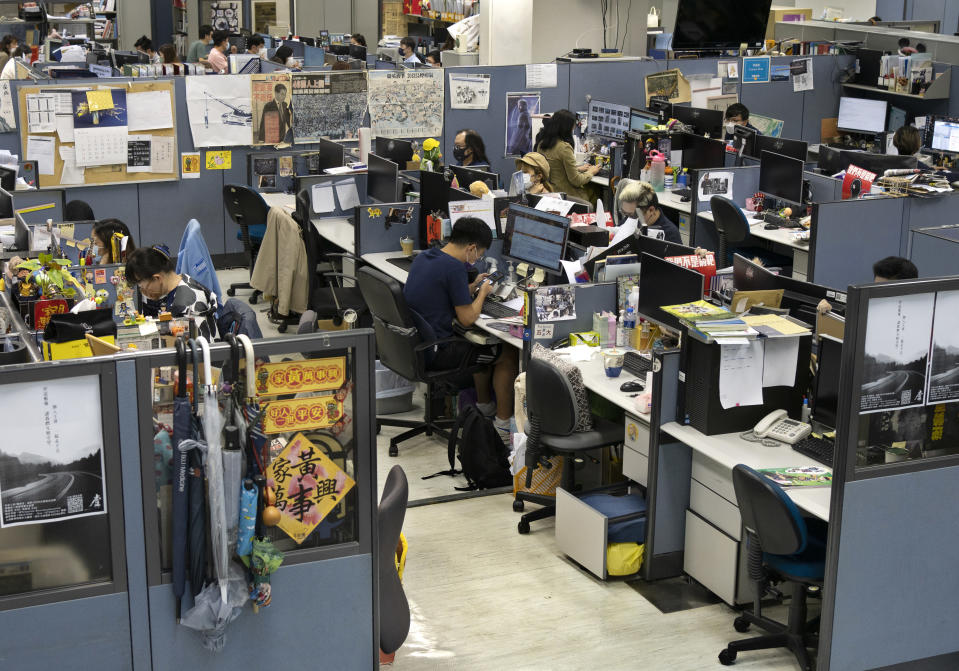 Reporters work at the news room of Apple Daily Monday, April 26, 2021 in Hong Kong. A newspaper that has advocated for greater democracy in Hong Kong came under further pressure Thursday, June 17, 2021, with the arrests of three top editors and two senior executives. (AP Photo/Vincent Yu)