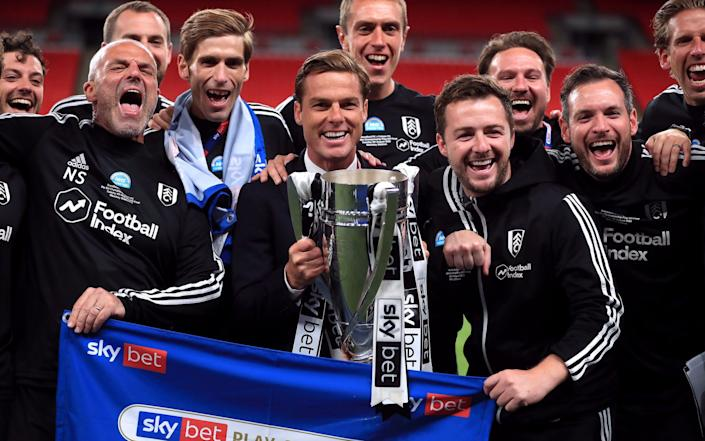 Scott Parker, pictured here holding the trophy with Fulham's backroom staff - PA