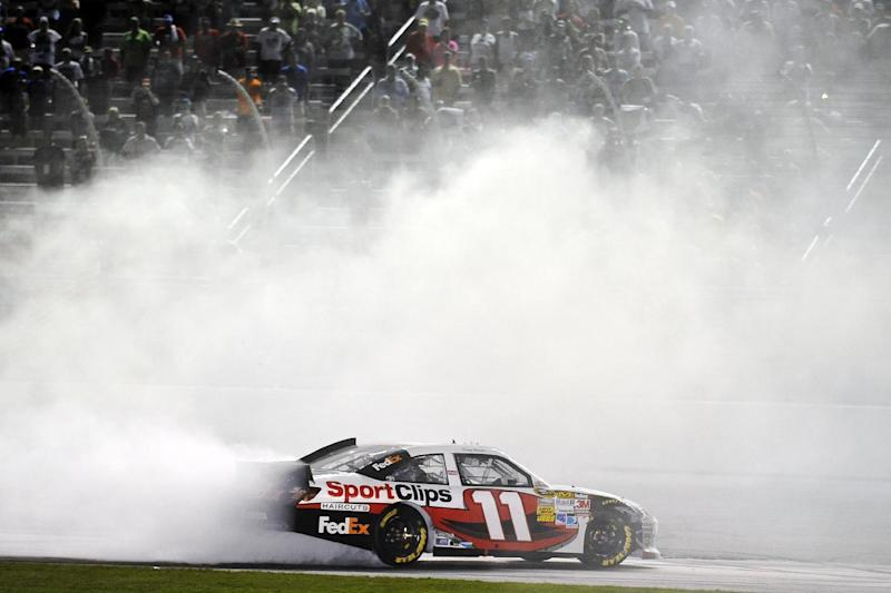 Denny Hamlin celebrates with a burnout after winning the NASCAR Sprint Cup Series auto race at Atlanta Motor Speedway, Sunday, Sept. 2, 2012, in Hampton, Ga. (AP Photo/Rainier Ehrhardt)