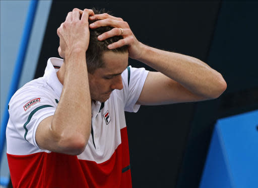 John Isner of the U.S. reacts after retiring from his third round singles match against Switzerland's Stan Wawrinka at the Australian Open tennis championship in Melbourne, Australia, Saturday, Jan. 25, 2020. (AP Photo/Andy Wong)