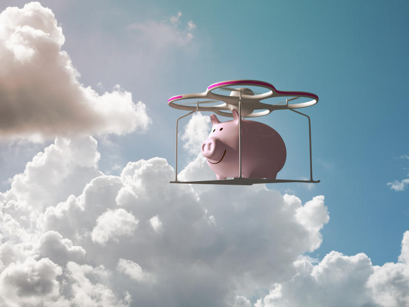 Piggy bank flying in the sky on a drone