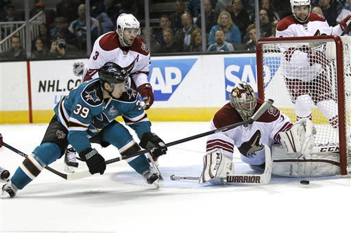 Phoenix Coyotes goalie Jason LaBarbera (1), blocks a goal attempt San Jose Sharks center Logan Couture (39) as Phoenix Coyotes defenseman Keith Yandle (3) watches during the first period of an NHL hockey game in San Jose, Calif., Saturday, March 30, 2013. (AP Photo/Tony Avelar)