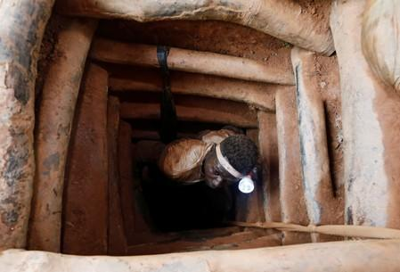 An informal gold miner exits a gold mine shaft at the site of Nsuaem-Top