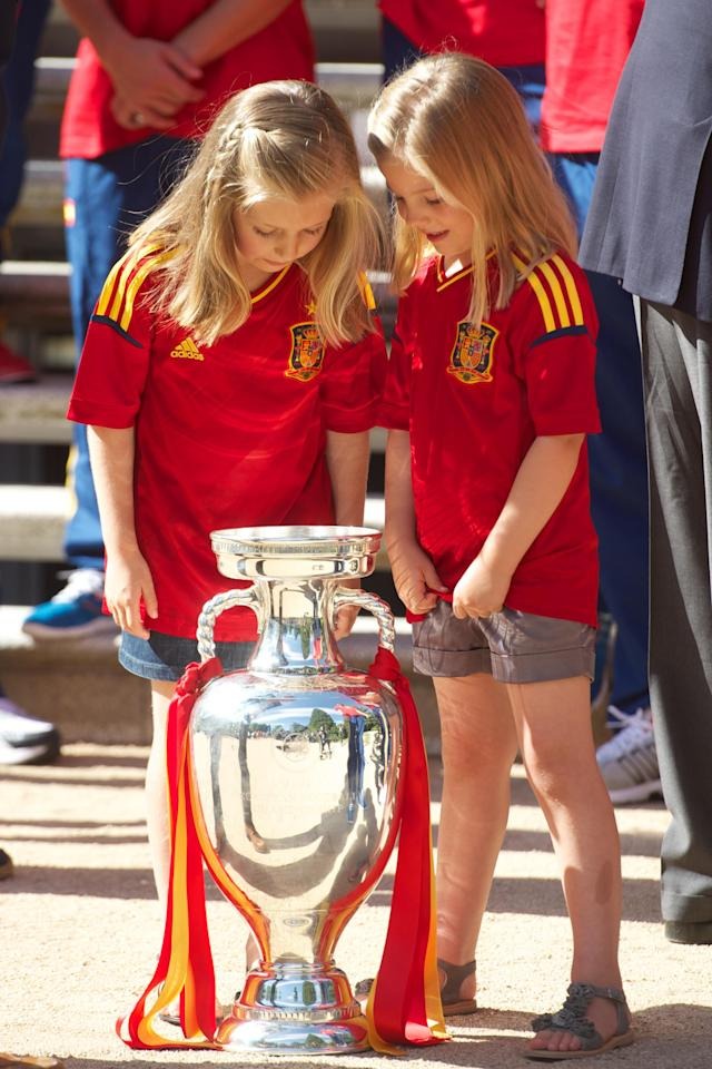 MADRID, SPAIN - JULY 02: Princess Leonor of Spain (L) and Princess Sofia of Spain (R) look at the UEFA EURO 2012 trophy as King Juan Carlos I of Spain receives players of Spain's victorious national football team at Zarzuela Palace on July 2, 2012 in Madrid, Spain. (Photo by Pool/Getty Images)
