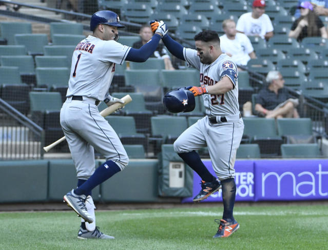 Houston Astros' Jose Altuve (27) is greeted by Carlos Correa (1) after hitting a home run against the Chicago White Sox during the third inning of game one of a baseball doubleheader, Tuesday, Aug. 13, 2019, in Chicago. (AP Photo/David Banks)