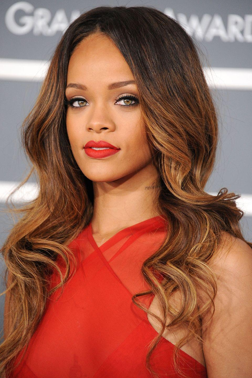 <p>Rihanna wears her caramel ombré hair long and in loose curls. </p>