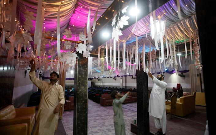 Workers finalise arrangements for the reopening of a wedding hall in Pakistan that has been closed since March, after the country has seen a steady decline in deaths and infections - AP