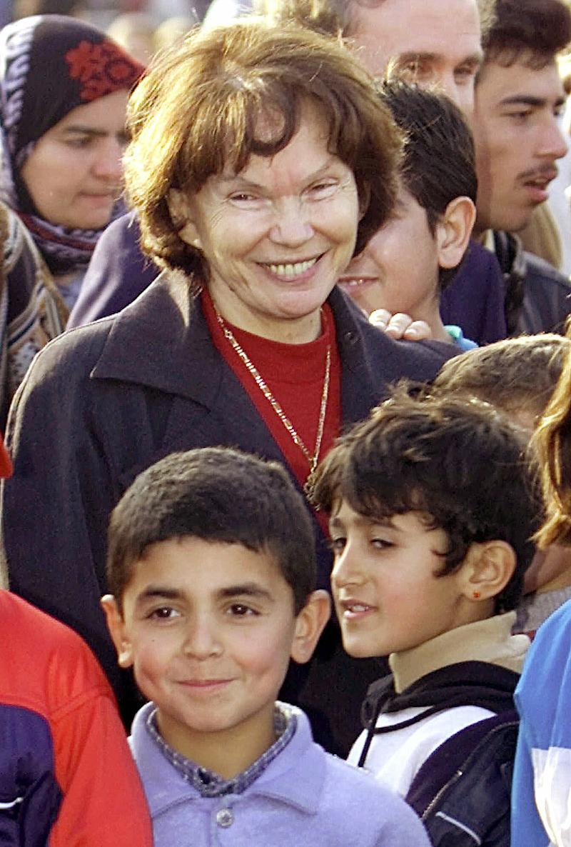 FILE - In this Feb. 20, 2001, file photo, former French first lady Danielle Mitterrand poses with Kurdish refugees as she visits a makeshift housing camp in Frejus, southern France.  Danielle Mitterrand, a member of the French Resistance and outspoken advocate for human rights who broke the mold as first lady alongside France's first Socialist president, has died it is announced Tuesday Nov. 22, 2011.  Mitterrand, who was 87, died overnight Monday to Tuesday Nov.22  2011, after being hospitalized at Georges Pompidou hospital in Paris for fatigue.  (AP Photo/Lionnel Cironneau, file)