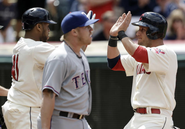 Cleveland Indians' Carlos Santana, left, and Yan Gomes, right, celebrate after both scored on a double by Michael Bourn hit off Texas Rangers relief pitcher Robbie Ross, center, in the sixth inning of a baseball game on Sunday, July 28, 2013, in Cleveland. (AP Photo/Tony Dejak)
