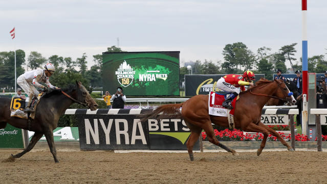 CORRECTS DAY AND DATE - Justify (1), with jockey Mike Smith up, crosses the finish line ahead of Gronkowski (6), with jockey Jose Ortiz up, to win the 150th running of the Belmont Stakes horse race and the Triple Crown, Saturday, June 9, 2018, in Elmont, N.Y. (AP Photo/Julie Jacobson)