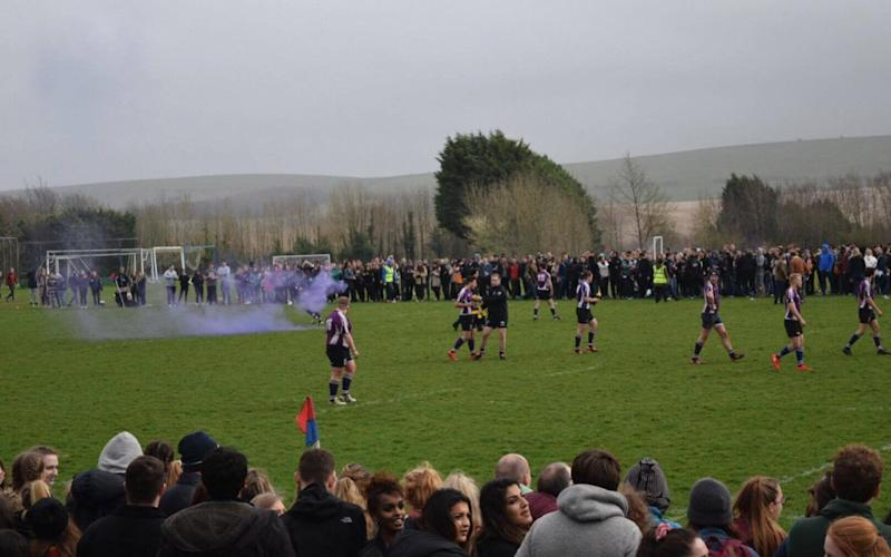 A flare was thrown onto the pitch during a rugby varsity match as police struggled to control supporters - Credit: The Tab