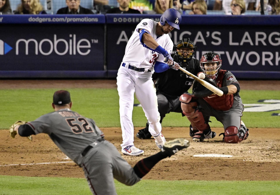 Los Angeles Dodgers' Cody Bellinger hits a solo home run off Arizona Diamondbacks starting pitcher Zack Godley, foreground, as catcher Alex Avila and home plate umpire Tripp Gibson watch during the fifth inning of a baseball game Saturday, March 30, 2019, in Los Angeles. (AP Photo/Mark J. Terrill)