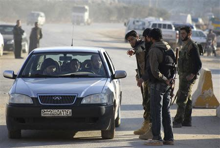 Islamist fighters man a checkpoint at the Syrian border crossing of Bab al-Hawa