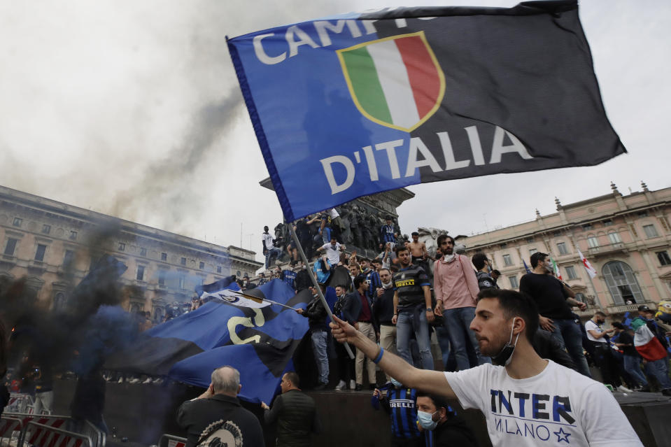 FILE - In this May 2, 2021, file photo, Inter Milan fans celebrate and shout slogans in Piazza Duomo square in front of the gothic cathedral after Inter Milan won its first Serie A title in more than a decade after second-placed Atalanta drew 1-1 at Sassuolo, in Milan, Italy. (AP Photo/Luca Bruno, File)