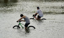 Cyclists peddle through floodwaters caused by the effects of Hurricane Ida near the New Orleans Marina, Monday, Aug. 30, 2021, in New Orleans, La. (AP Photo/Eric Gay)