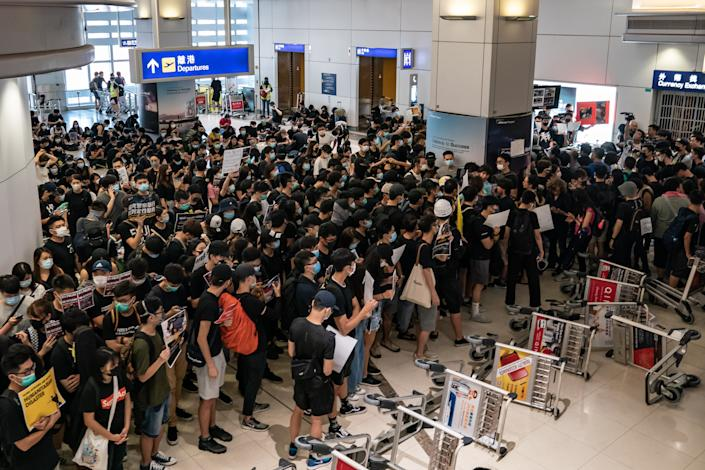 Protesters hold placards as they block the departure gate of the Hong Kong International Airport Terminal 2 during a demonstration on August 13, 2019 in Hong Kong, China. (Photo: Anthony Kwan/NurPhoto via Getty Images)