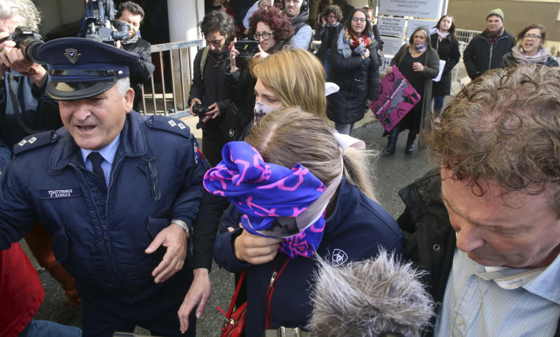 A 19-year old British woman, center, covers her face as she leaves from the Famagusta court after her trial, in Paralimni, Cyprus, Monday, Dec. 30, 2019. A Cyprus court on Monday found a 19 year-old British woman guilty of fabricating claims that she was gang raped by 12 Israeli men. (AP Photo/Philippos Christou)