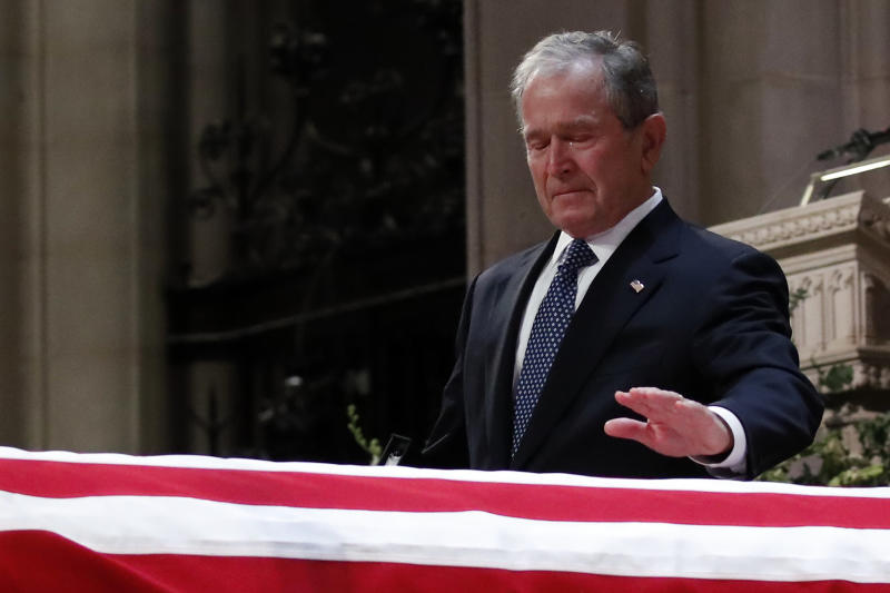 """Bush touches his father's casket during the funeral ceremony. He praised him as""""the best father a son or daughter could have."""" (ASSOCIATED PRESS)"""