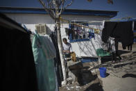 A woman washes her clothes at the Pan de Vida shelter in Ciudad Juarez, Mexico, Friday, Feb. 19, 2021. After waiting months and sometimes years in Mexico, people seeking asylum in the United States are being allowed into the country starting Friday as they wait for courts to decide on their cases, unwinding one of the Trump administration's signature immigration policies that President Joe Biden vowed to end. (AP Photo/Christian Chavez)
