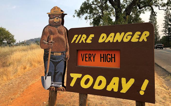 A roadside sign outside Colfax, Calif., warns of the threat of wildfires on Aug. 4. (Photo: Jim Christie/Reuters)