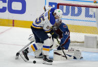 St. Louis Blues center Jordan Kyrou, front, struggles to direct a shot on Colorado Avalanche goaltender Philipp Grubauer during the first period of an NHL hockey game Wednesday, Jan. 13, 2021, in Denver. (AP Photo/David Zalubowski)