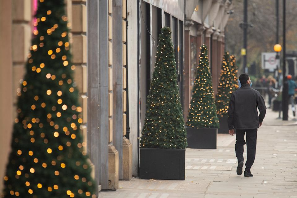 A man walks past Christmas lights outside shops in central London, as England approaches the final week of a four week national lockdown to curb the spread of coronavirus. (Photo by Dominic Lipinski/PA Images via Getty Images)