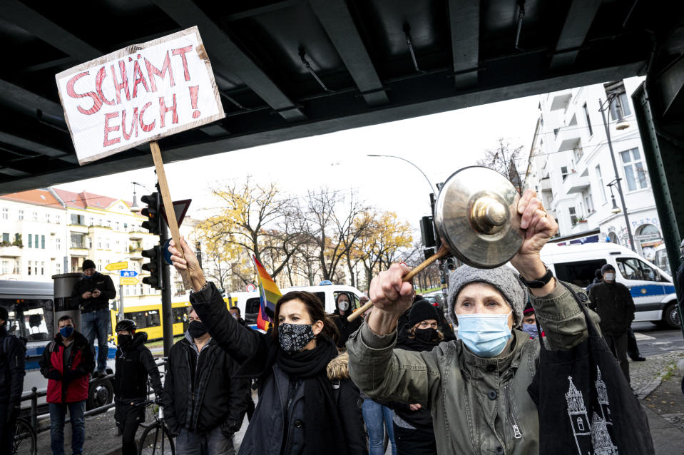 Counter demonstrators shows a poster reading: 'shame on you' as the protest against a so called 'silent march' against the corona policy of the federal government, at the district Prenzlauer Berg in Berlin Germany, Sunday, Nov. 22, 2020. (Fabian Sommer/dpa via AP)