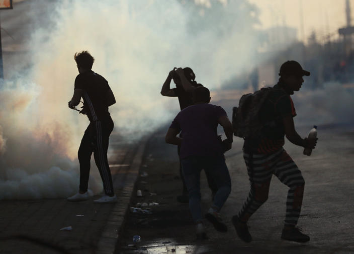 Iraqi security forces fire tear gas to disperse anti-government protesters during a demonstration in Baghdad, Iraq, Saturday, Oct. 5, 2019. The spontaneous protests which started Tuesday in Baghdad and southern cities were sparked by endemic corruption and lack of jobs. Security responded with a harsh crackdown, leaving more than 70 killed. (AP Photo/Hadi Mizban)