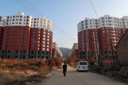 Man walks near a shantytown to be redeveloped, in front of apartment buildings, in Fu county in the south of Yanan