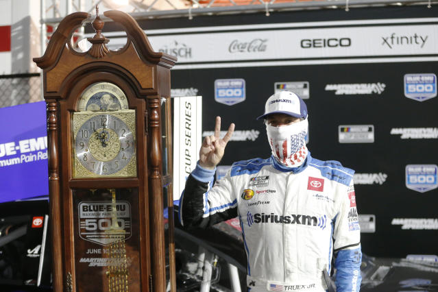 Martin Truex Jr. celebrates with his grandfather clock trophy after winning a NASCAR Cup Series auto race Wednesday, June 10, 2020, in Martinsville, Va. (AP Photo/Steve Helber)