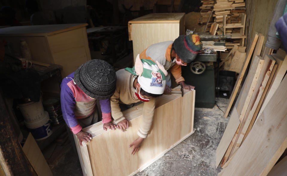 Three of the Delgado children, from right, Yuri, 11, Wendi, 9, and Alison, 8, make a drawer in the family carpentry workshop in El Alto, Bolivia, Wednesday, Sept. 2, 2020. In a country where informal employment makes up 70% of the economy, the closure of schools because of the new coronavirus pandemic puts more kids like the Delgados to work. (AP Photo/Juan Karita)