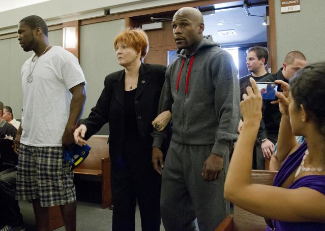 Floyd Mayweather Jr., right, walks into court escorted by his attorney Karen Winckler, center, and 50 Cent, left, to begin his 90-day jail term, Friday, June 1, 2012, in Las Vegas. The undefeated five-division champion surrendered Friday before the judge who sentenced him in December for attacking his ex-girlfriend in September 2010 while two of their children watched. (AP Photo/Julie Jacobson)