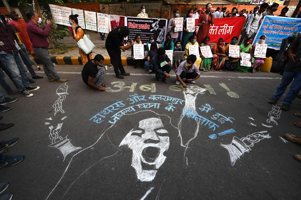 <p>Demonstrators paint a floor mural as they protest against the alleged gang-rape and murder of a 19-year-old woman in Uttar Pradesh state</p> (Getty)