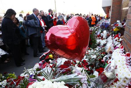 Fans lay flowers by the Shankly gates before a memorial service to mark the 25th anniversary of the Hillsborough disaster at Anfield in Liverpool, northern England April 15, 2014. REUTERS/Darren Staples