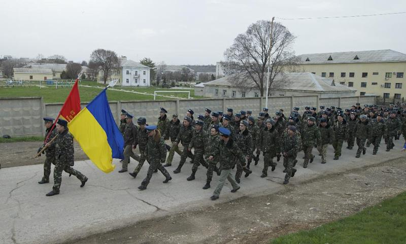 Ukrainian officers march at the Belbek air base, outside Sevastopol, Ukraine, on Tuesday, March 4, 2014. Russian troops, who had taken control over Belbek airbase, fired warning shots in the air as around 300 Ukrainian officers marched towards them to demand their jobs back. (AP Photo/Ivan Sekretarev)