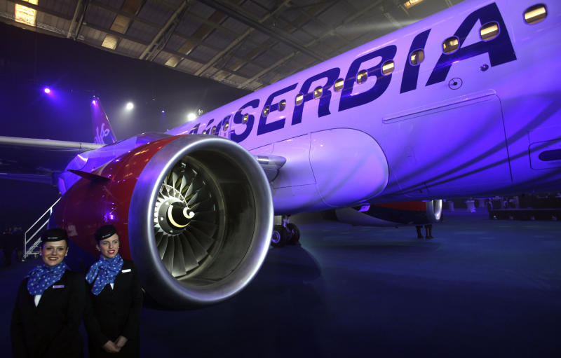 "New cabin crew members stand by the first Airbus A319-100 aircraft in Air Serbia livery parked in a hangar during the inauguration ceremony at Belgrade's Nikola Tesla Airport, Serbia, Friday, Oct. 25, 2013. Officials say that Air Serbia, Balkan country's new national carrier partly owned by Etihad Airways, formally starts flying this weekend, spelling the end for the old loss-making JAT Airways. Air Serbia's chief manager Dane Kondic said Friday that the company's inaugural flight will take place on Saturday to Abu Dhabi, United Arab Emirates. He says that ""it is an important flight that will mark a crossroads."" Kondic and Serbia's deputy prime minister Aleksandar Vucic unveiled at a ceremony at Belgrade's airport an Airbus A319 plane bearing a double-headed eagle logo in Serbia's national, red, white and blue colors. Vucic says Air Serbia hopes to become the leading regional airline. (AP Photo/Darko Vojinovic)"