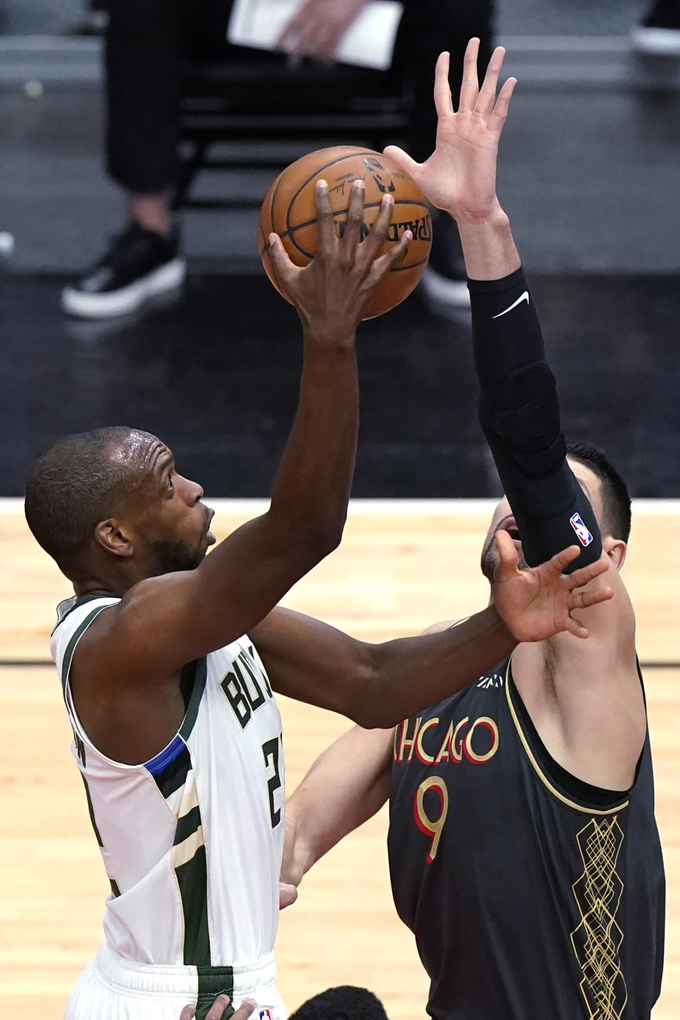 Milwaukee Bucks forward Khris Middleton, left, drives to the basket against Chicago Bulls center Nikola Vucevic during the first half of an NBA basketball game in Chicago, Friday, April 30, 2021. (AP Photo/Nam Y. Huh)