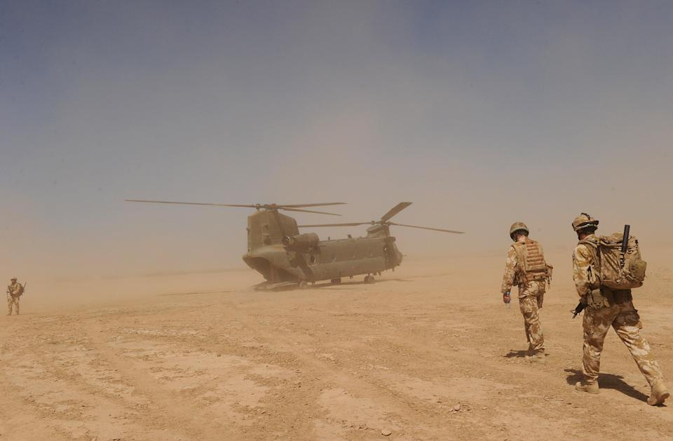 British soldiers walk to a military helicopter near the Pimon military camp in Nad-e Ali district of Helmand province, Afghanistan  (AFP via Getty Images)