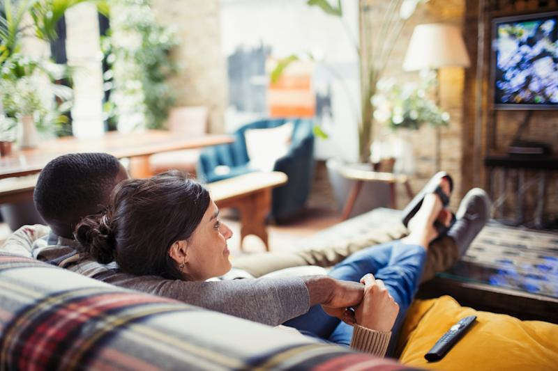 Affectionate young couple watching TV on living room sofa. Photo: Getty
